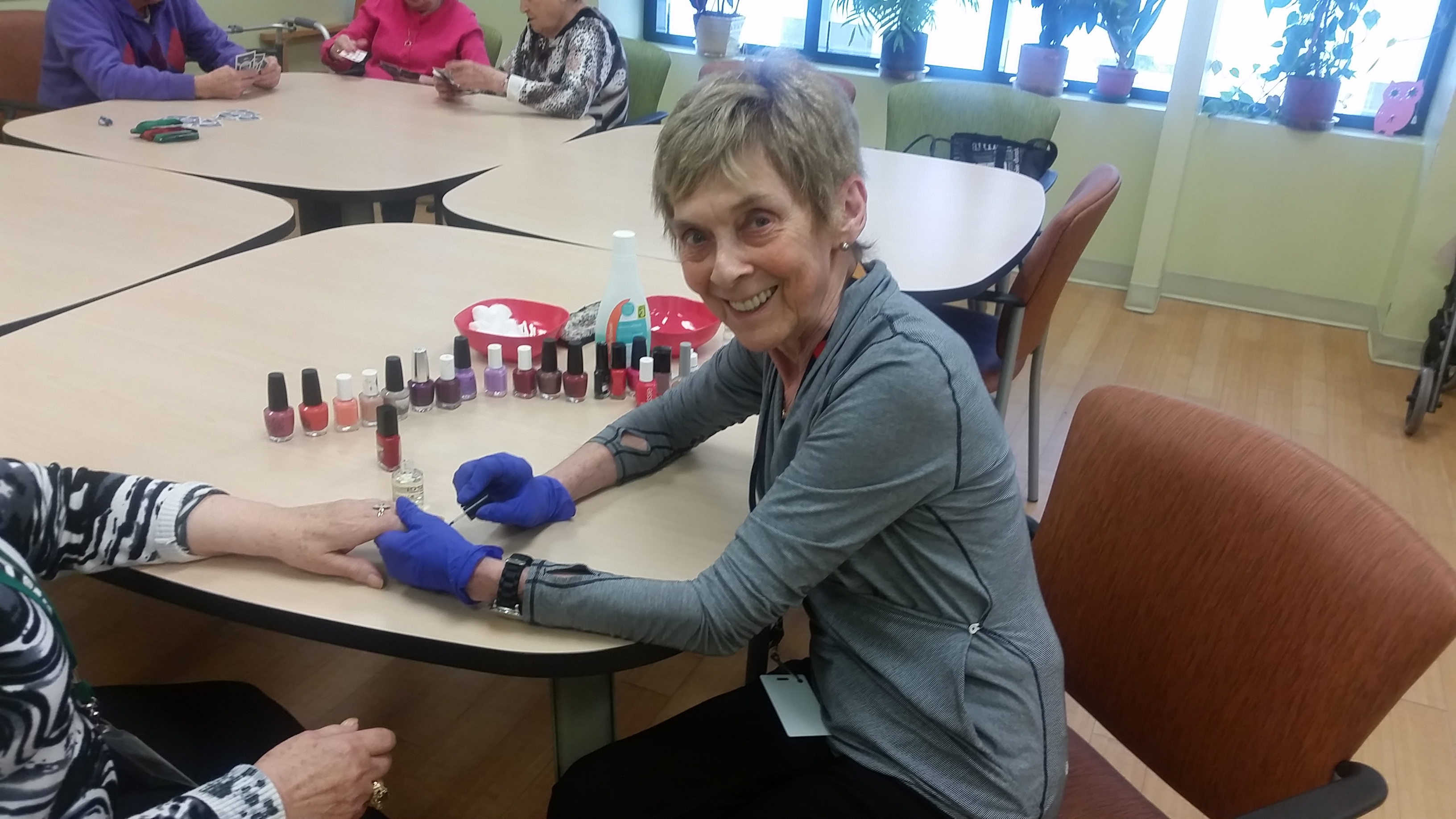 image of a volunteer painting a client's nails