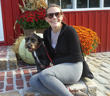 Image of a woman sitting outside in front of a house with a dog.