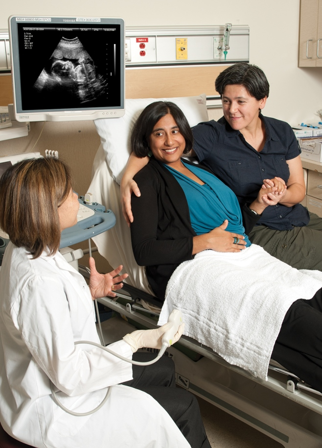 image shows a couple having an ultrasound of a pregnancy with an ultrasound technician