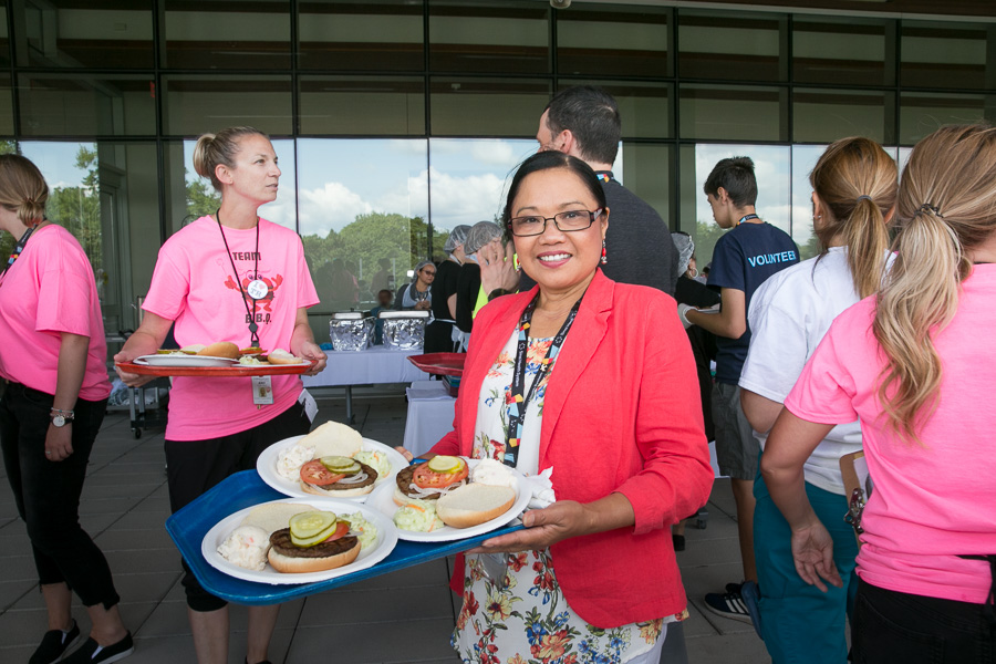 Staff member carrying a tray of burgers at the patient and family barbecue