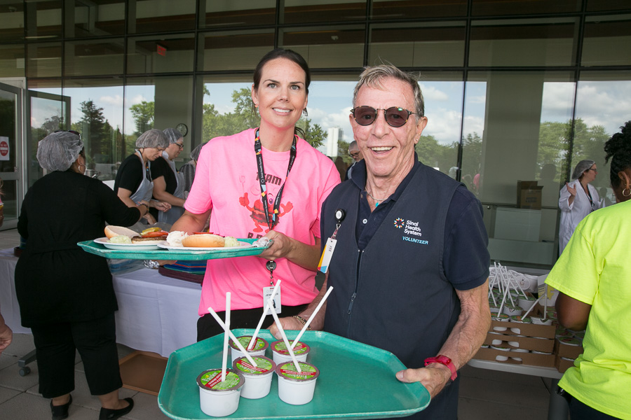 Staff member and volunteer with trays to serve food at the patient and family barbecue