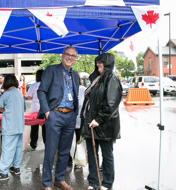 Sinai Health System President and CEO Gary Newton speaking with a staff member at the staff barbecue and Mount Sinai Hospital.