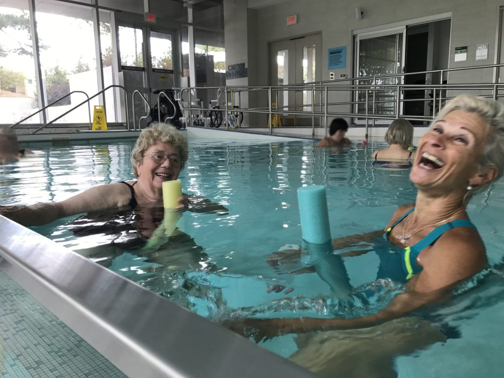 A participant in a pool fitness class and the instructor in the pool