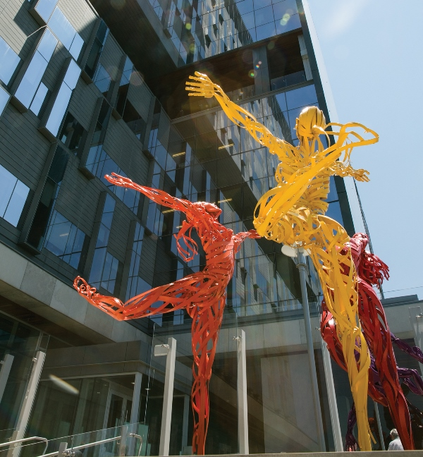 Image of sculptures in bright colours depicting life-sized human figures dancing.