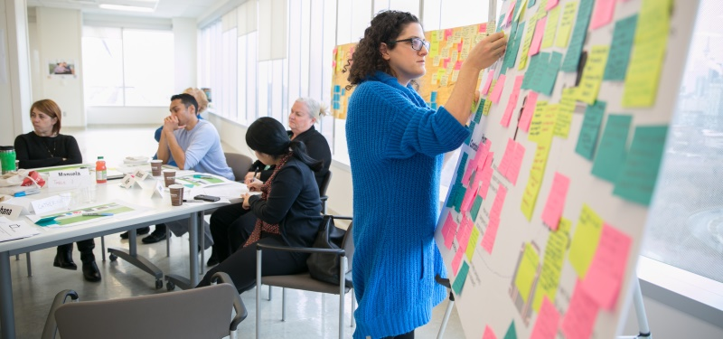 A staff member posts a note to a board full of colourful sticky notes, other people sit at a table behind her at an event where staff members and caregivers brainstormed in small groups