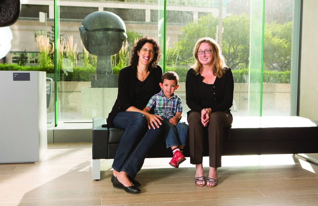 Image shows physician Dr. Candice Silversides sitting on a bench with a patient and the patient's son