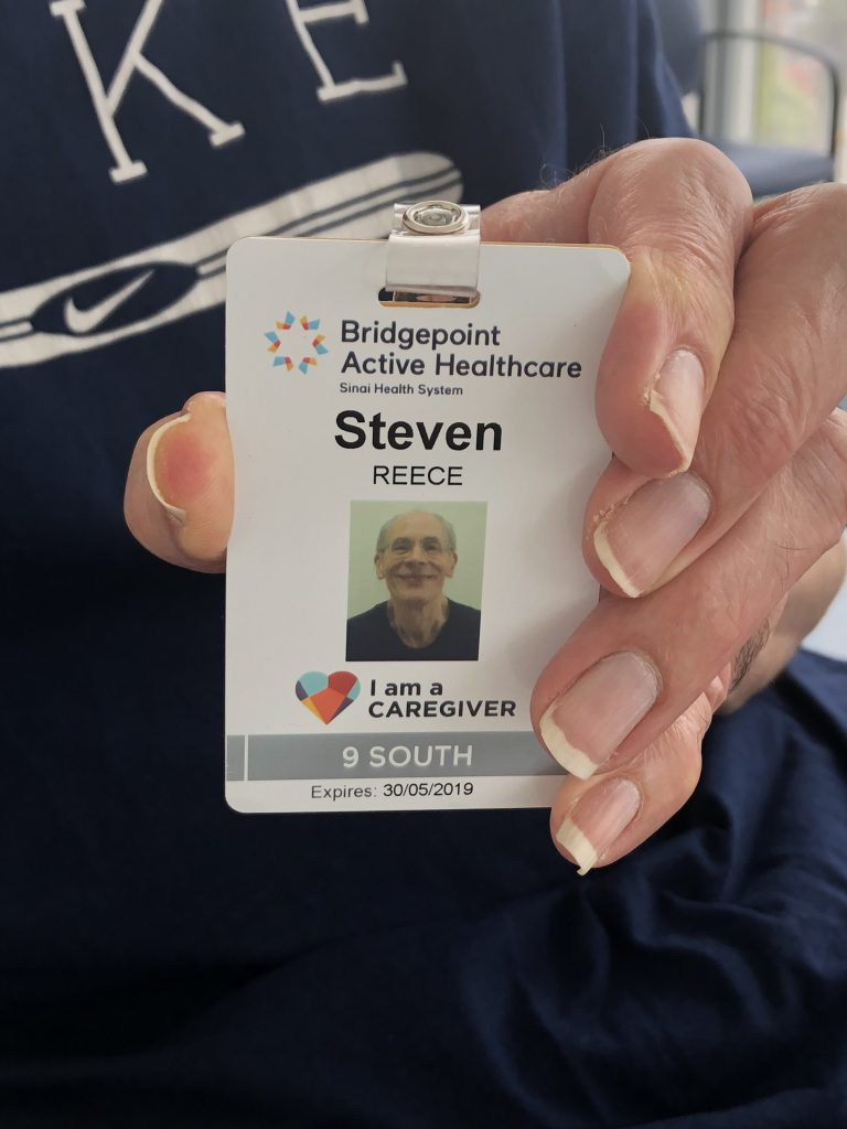 Family caregiver holding new identification badge for Bridgepoint's Family Presence Policy