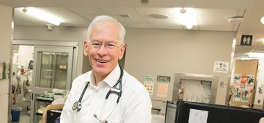 Photo is head shot of Dr. Don Melady with stethoscope on. Emergency Department is visible in the background