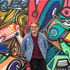 summer student standing in front of brightly painted brick wall