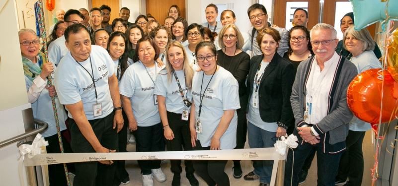 A large group of employees cuts a ribbon to mark the opening of a new unit at the hospital. One person at the front holds the scissors near the ribbon.