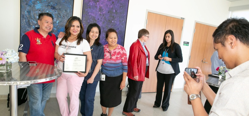 An employee who has received an award certificate at an awards celebration stands holding the certificate up with a group of her colleagues as another employee takes a photo.