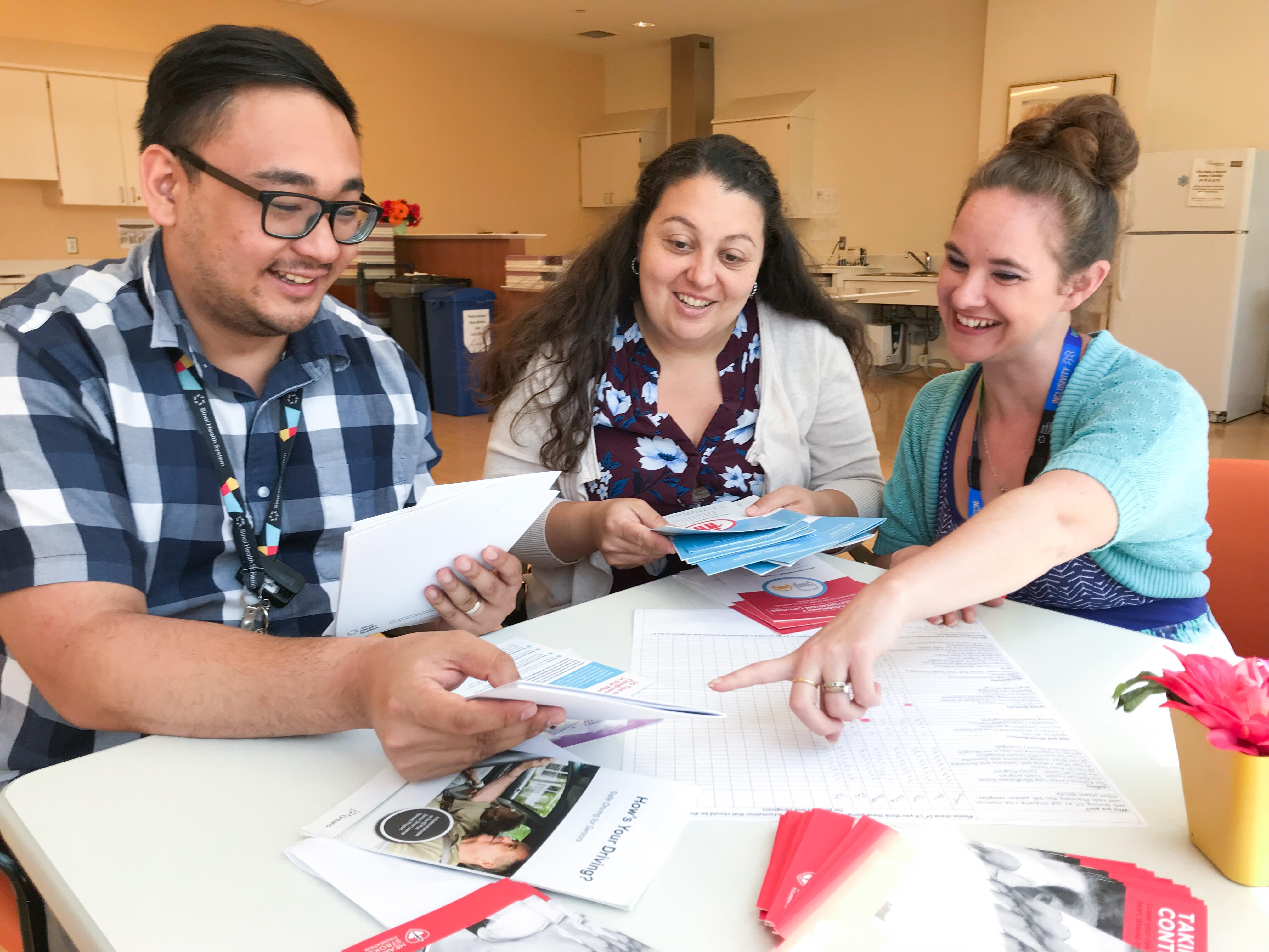 Photo shows three Bridgepoint clinical employees sitting at a table with some patient education brochures spread out. The employees are discussing the brochures