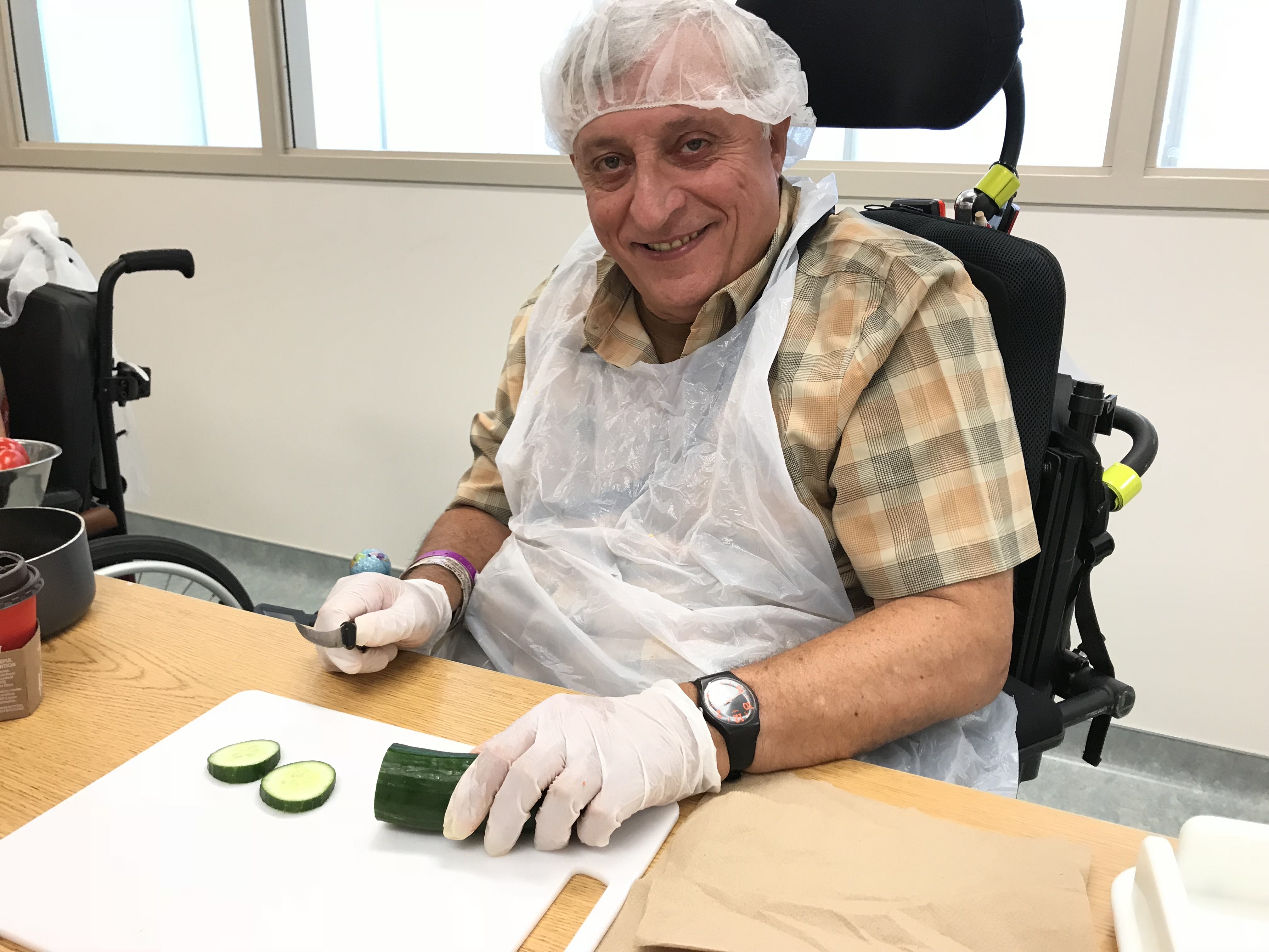 A man wearing an apron, hair net and gloves chops a cucumber at a table.