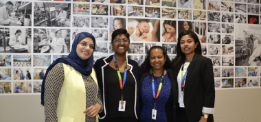 four women standing in front of a wall with hospital images behind them.