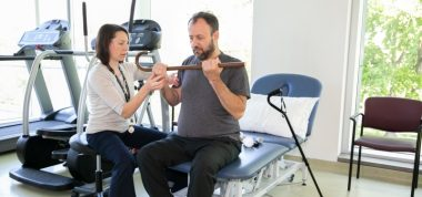 a physiotherapist and a patient sitting in a physiotherapy gym. The patient is doing an exercise where he is holding up a cane with both hands as the physiotherapist checks that he is using the correct form for the exercise