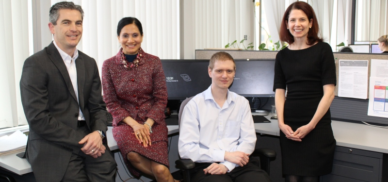 Four employees in an office looking at the camera, smiling