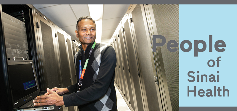 A man standing in a computer data centre with server cabinets. He's standing at a computer looking just off of the camera smiling
