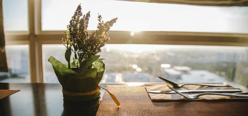 A small potted plant with flowers sits on a kitchen table with a place set for dining. There is a window and sunlight coming in the background
