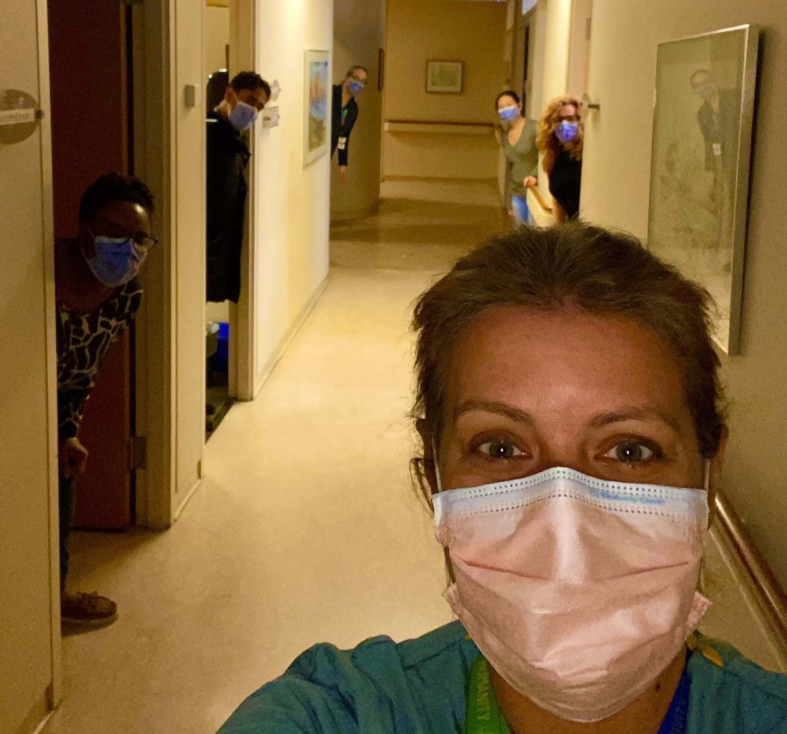 hospital employees in a hallway leaning out of office doors. They are wearing masks.