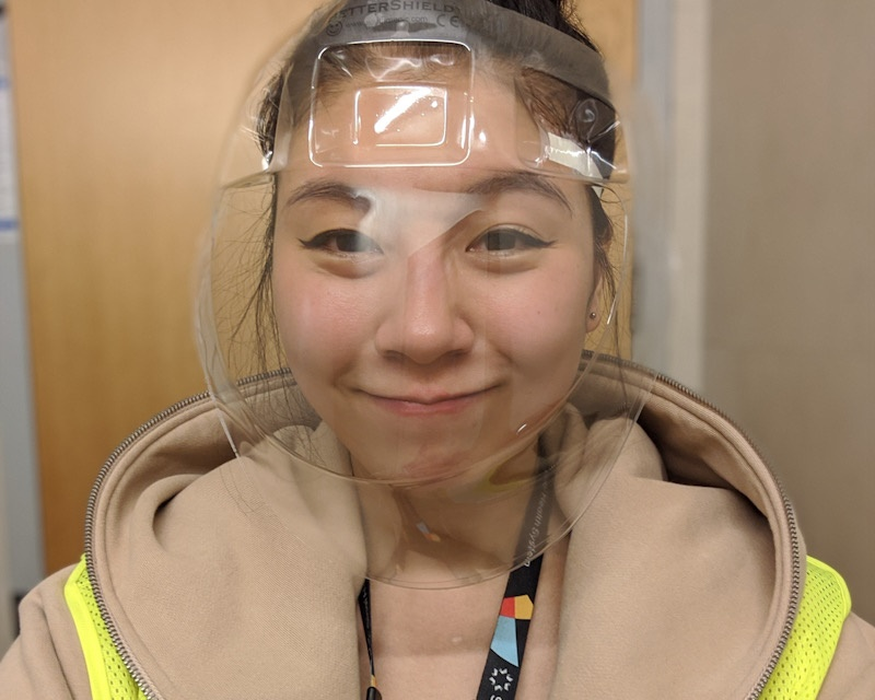 A woman wearing a protective clear plastic face shield looks at the camera smiling