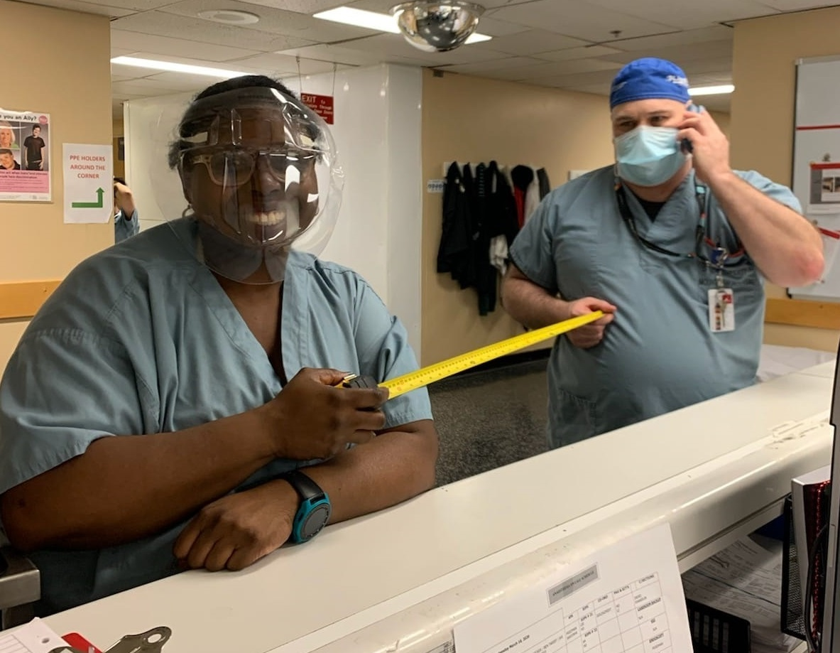 A woman in a face shield and scrubs and a man in a mask and scrubs standing near a reception desk in a hospital. They are holding a measuring tape extended between them.