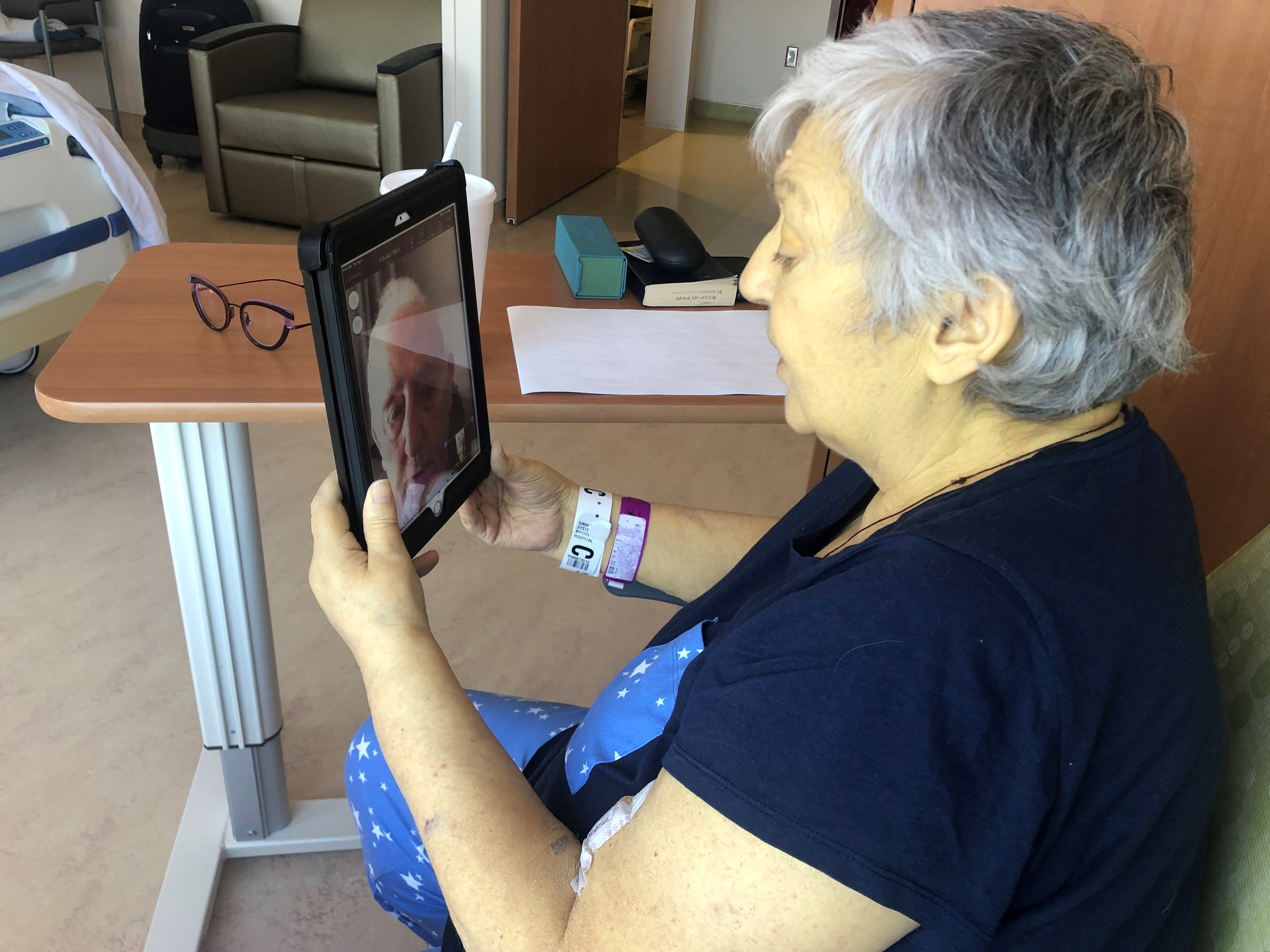 A woman seated in a hospital room holds up a tablet while video conferencing with her family