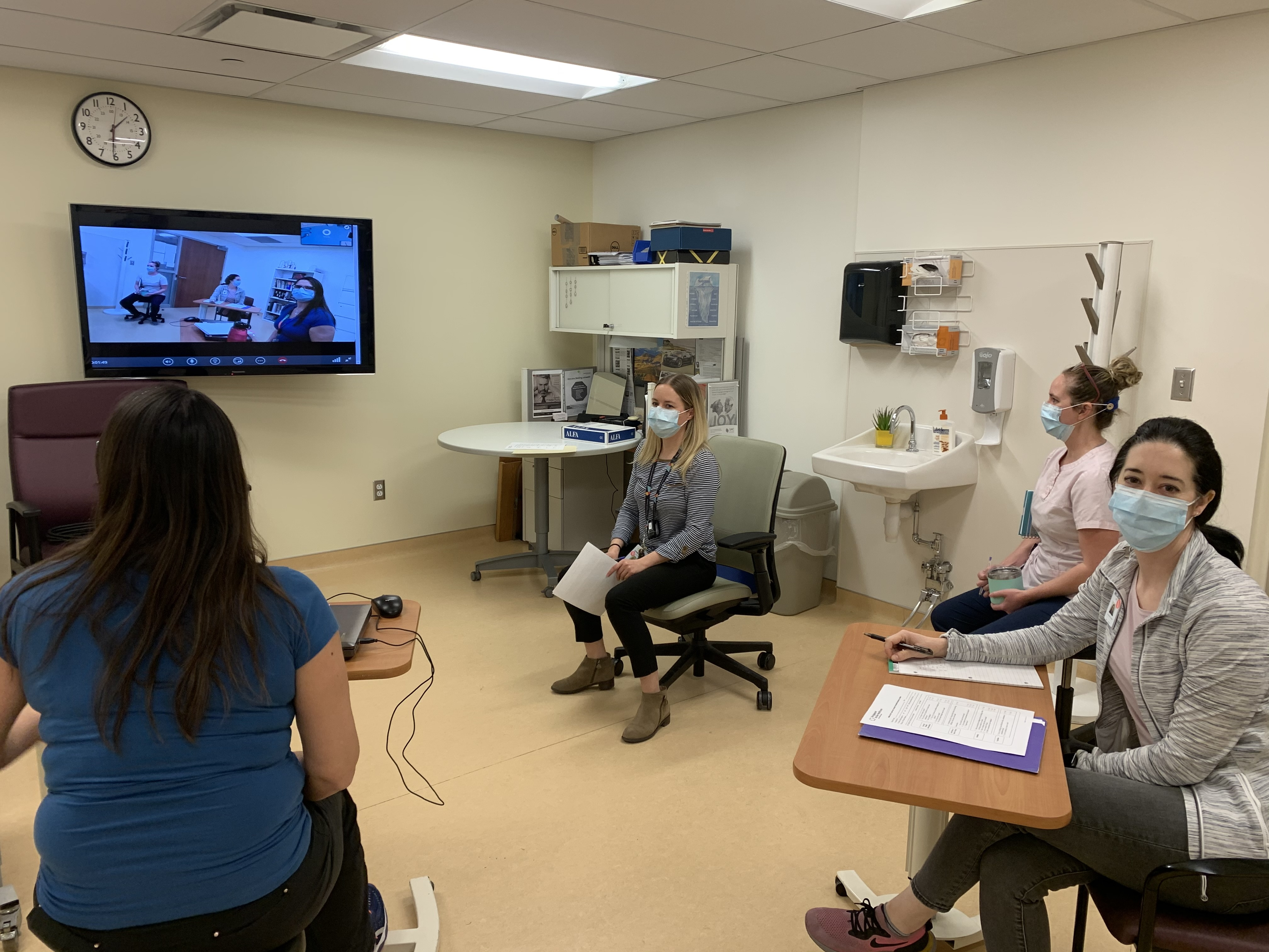 Health care workers wearing masks, sitting in a room, in front of a large television, waiting for a video conference call to start.