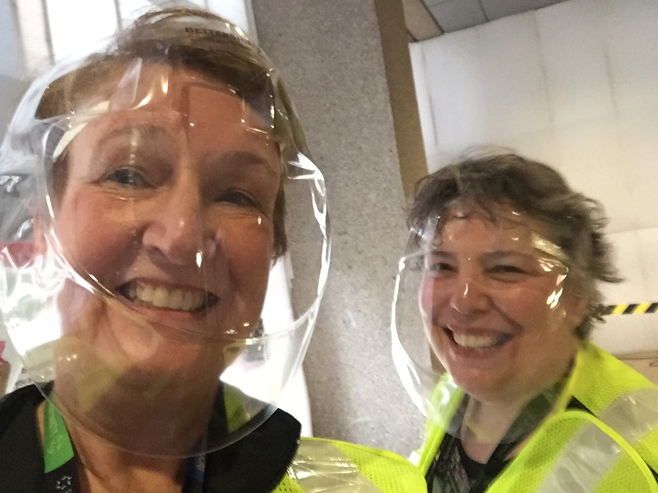Two women in reflective vests and face shields looking at the camera, smiling