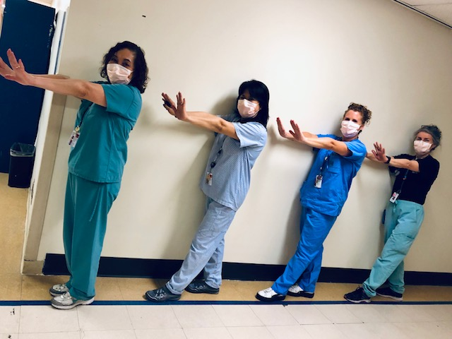 four hospital employees wearing scrubs and masks standing in front of a wall. They are facing perpendicular to the camera with their arms outstretched at shoulder height.