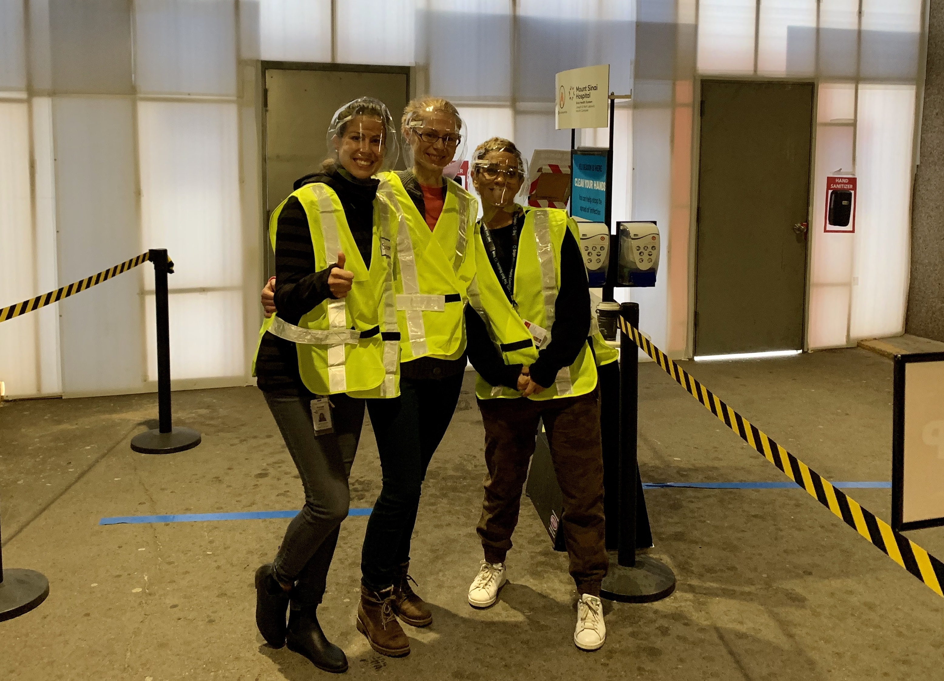 Three health care employees wearing reflective safety vests and face shields standing outside the hospital entrance. They are looking at the camera, smiling.