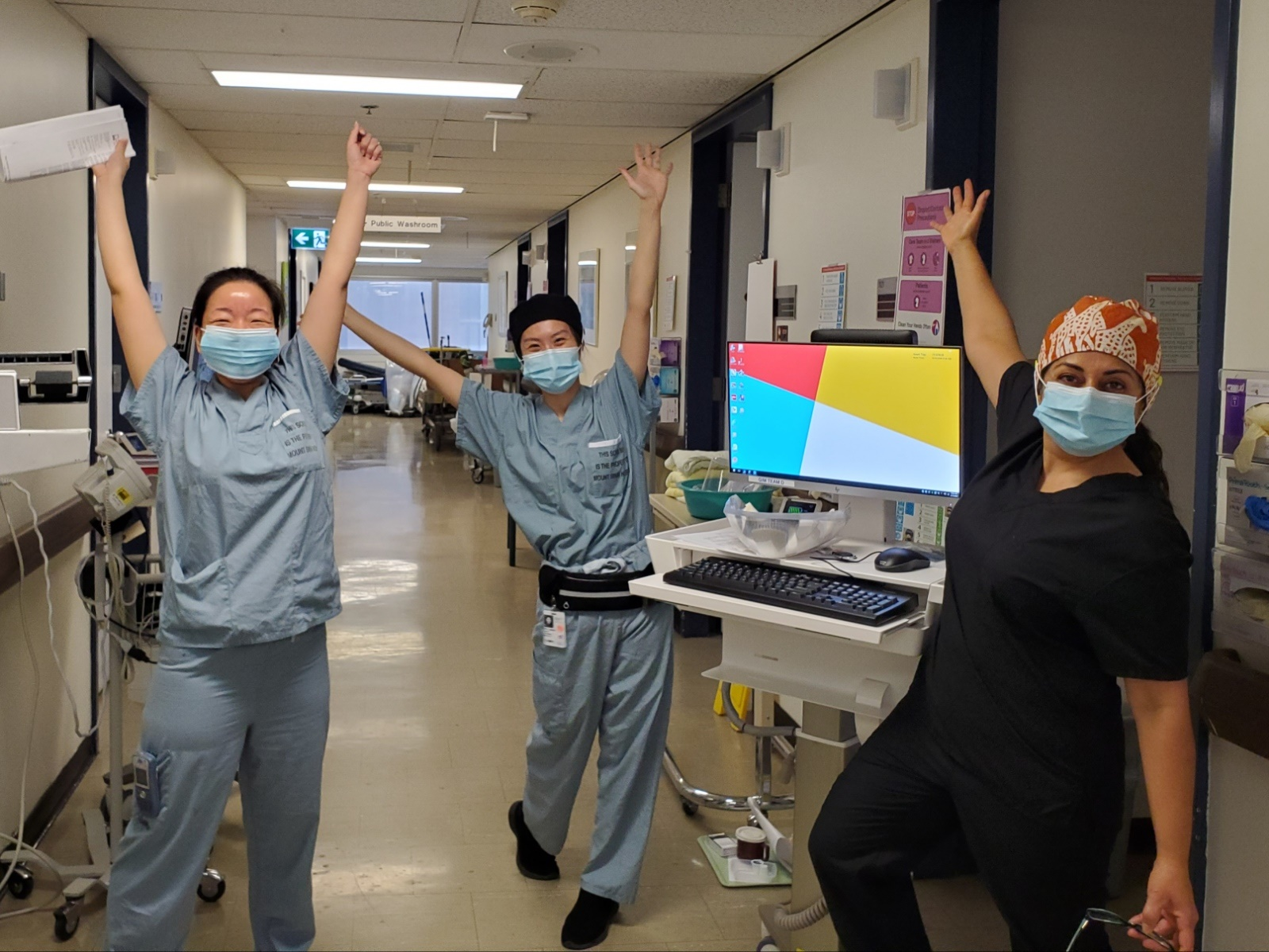 Three nurses in a hospital hallway with medical equipment. They are wearing masks and scrubs and looking at the camera with their hands in the air, celebrating