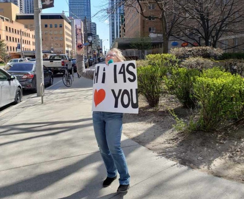 A woman on a sidewalk in a city. She is holding a sign and looking up. The signs Hi  14-S and has a heart.