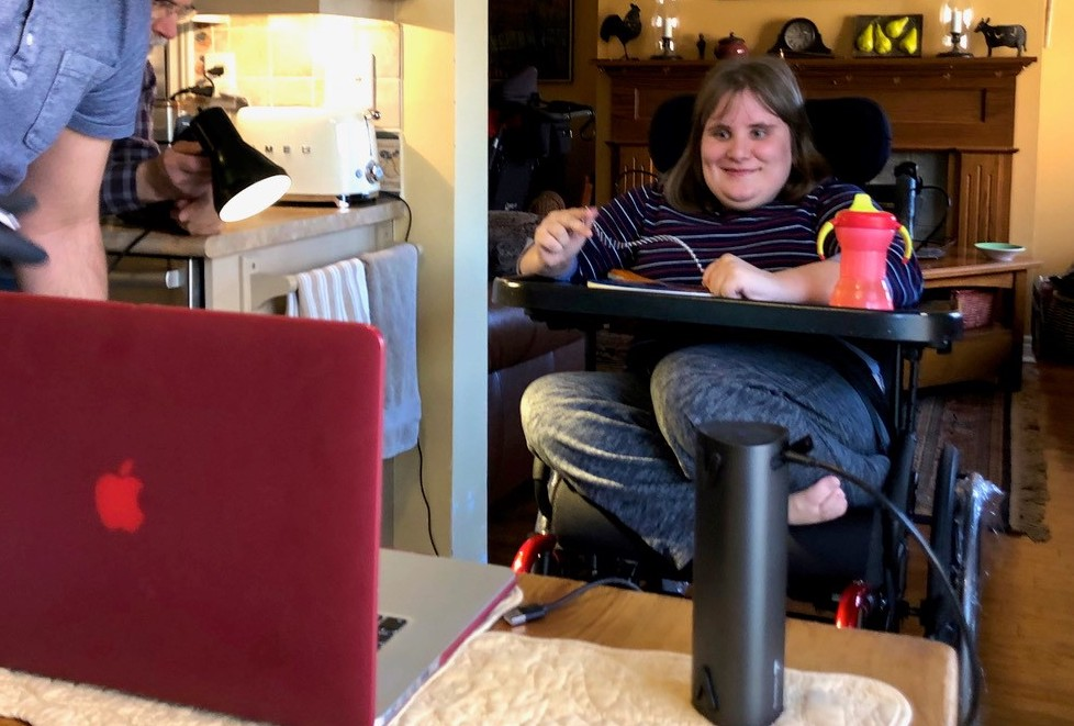 a woman in a power wheelchair looking at a laptop on a table.
