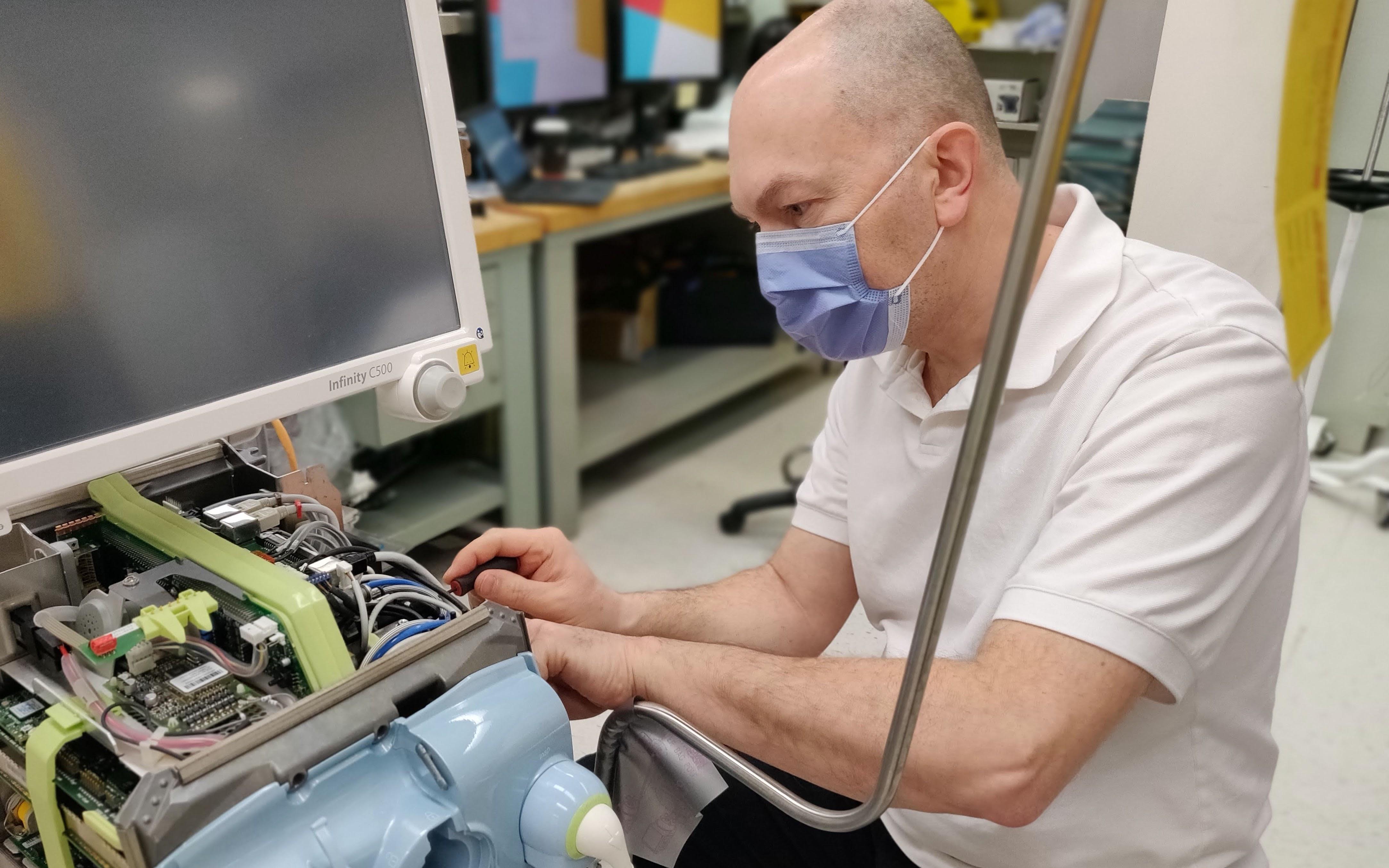 A man repairing a piece of medical equipment