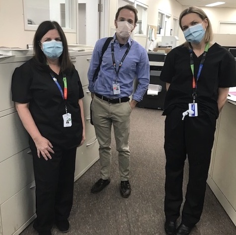 Three hospital employees in an office wearing masks. Two are wearing scrubs. Looking at the camera