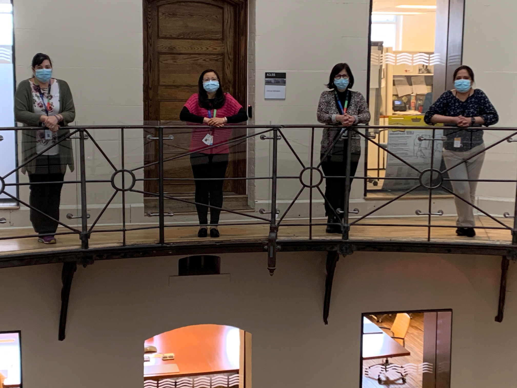 Four hospital employees wearing masks standing on  a second-floor walk way with an iron railing. They are  looking at the camera.