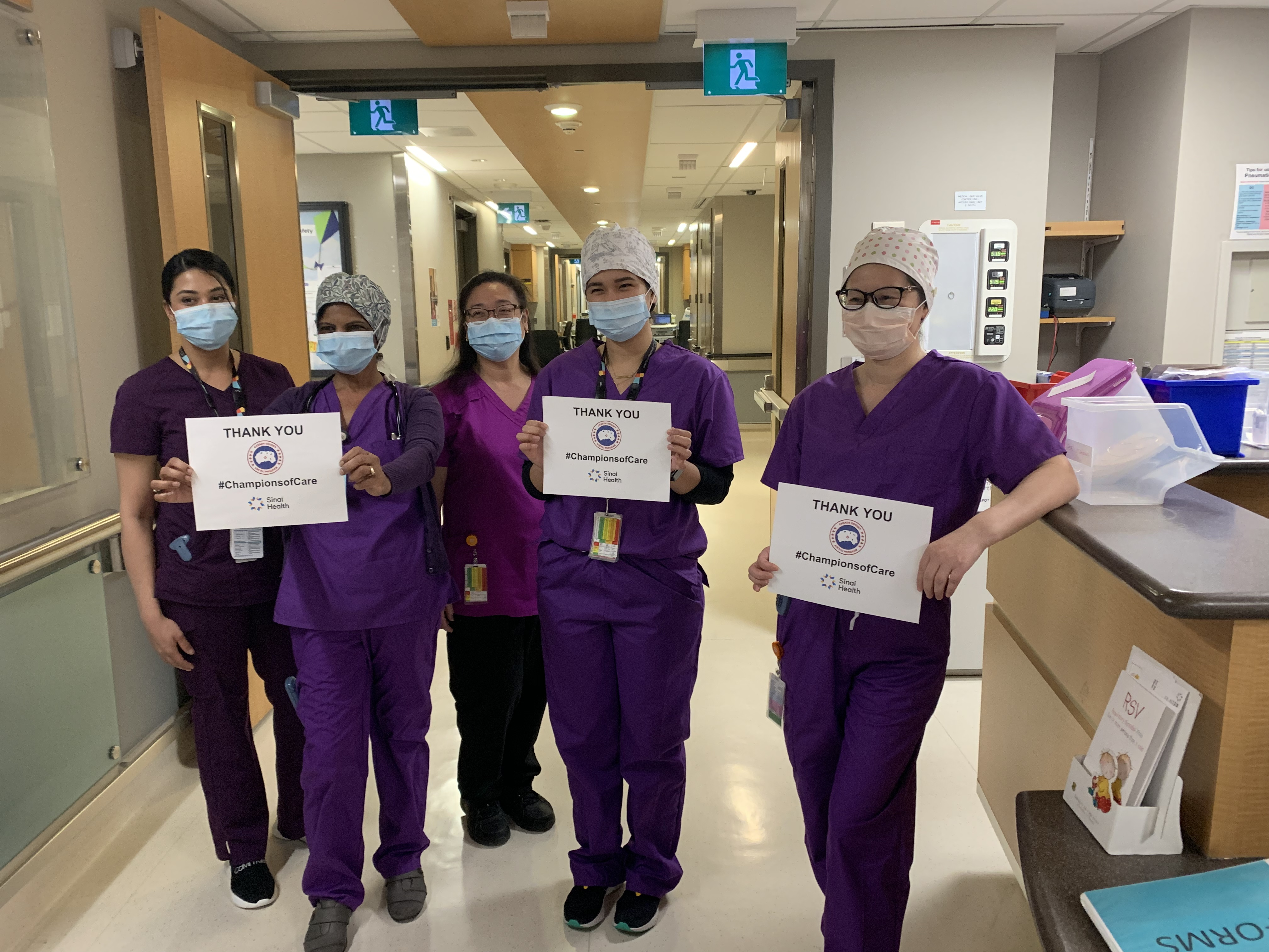 Nurses wearing purple scrubs in the hallway of a hospital. They are holding signs that say Thank You