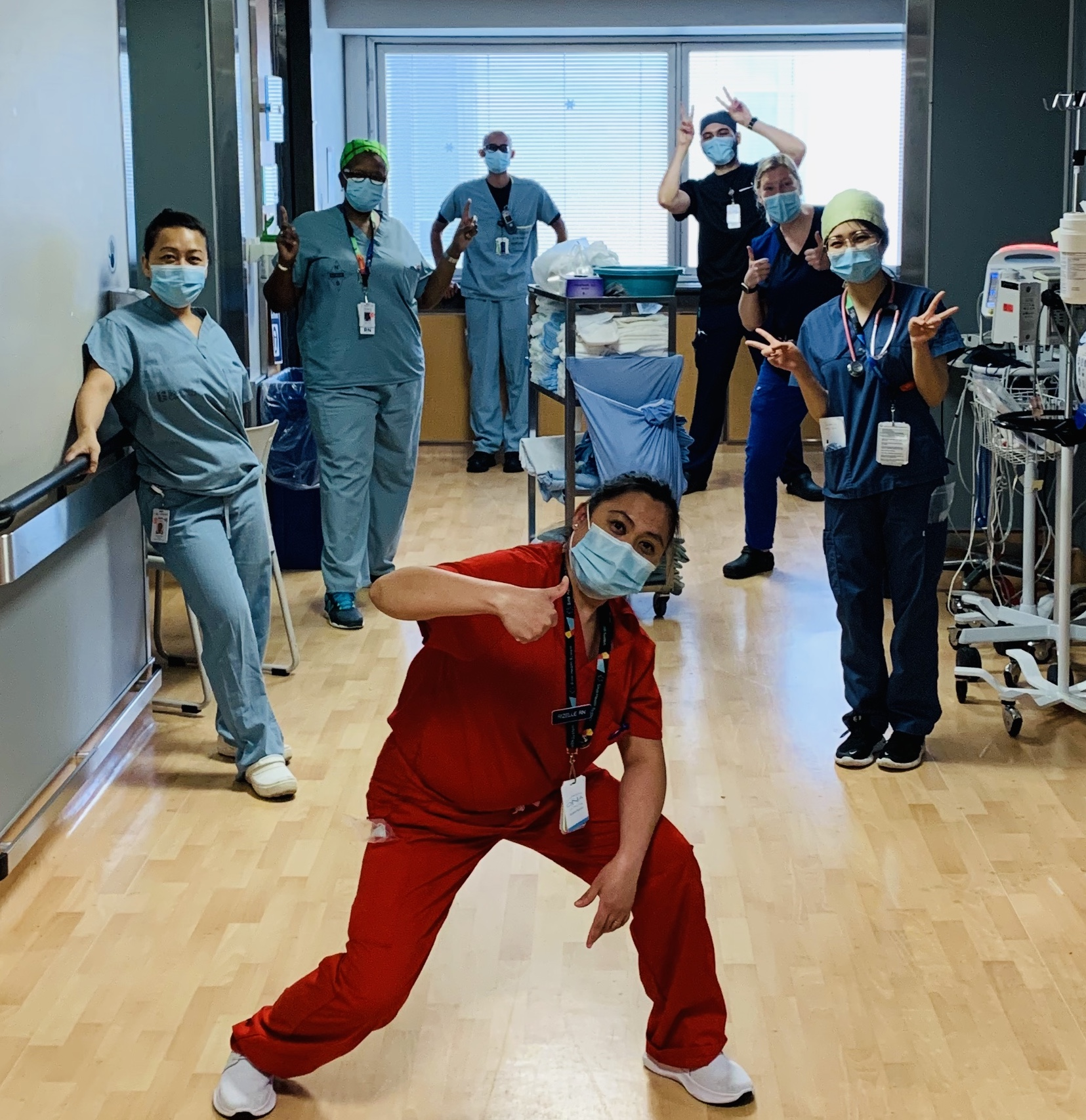 Hospital employees in a hospital hallway with medical equipment in the background. They are wearing scrubs and masks and standing apart from each other. Some are making peace signs or thumbs up signs with their hands.