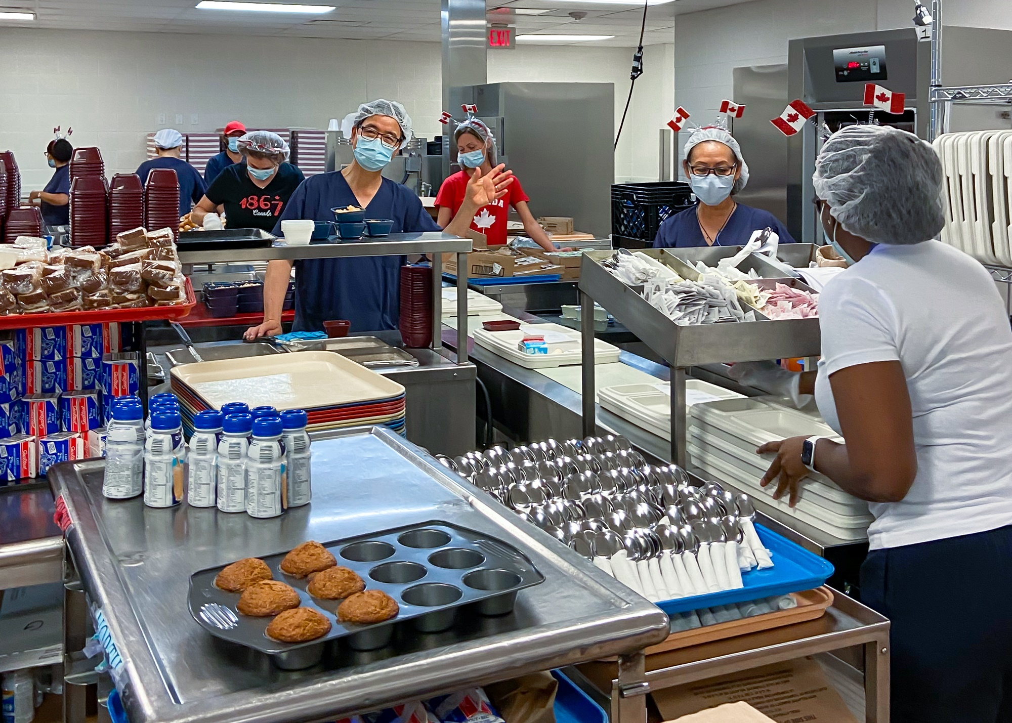 Employees in a large industrial kitchen working on assembling meal trays. They are wearing procedure masks and hair nets. Some have small Canadian flags sticking up from their hair.