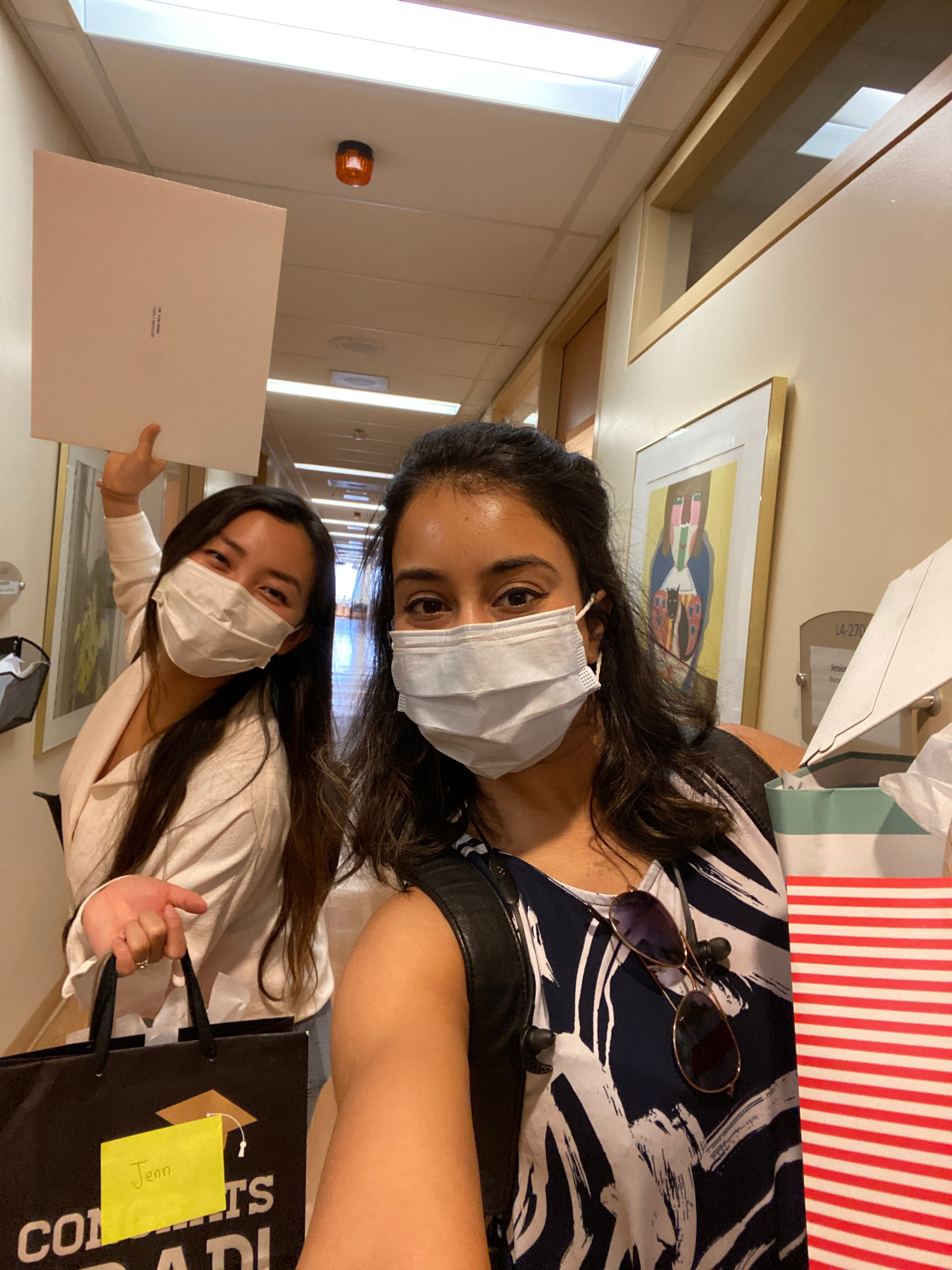 Two women in a selfie image standing in a hallway holding gift bags and evelopes. they are wearing masks and looking at the camera