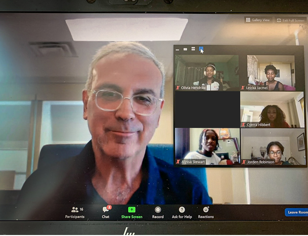 a man looking at the camera during a video chat on one side there are six images of the other people on the video chat looking at the camera