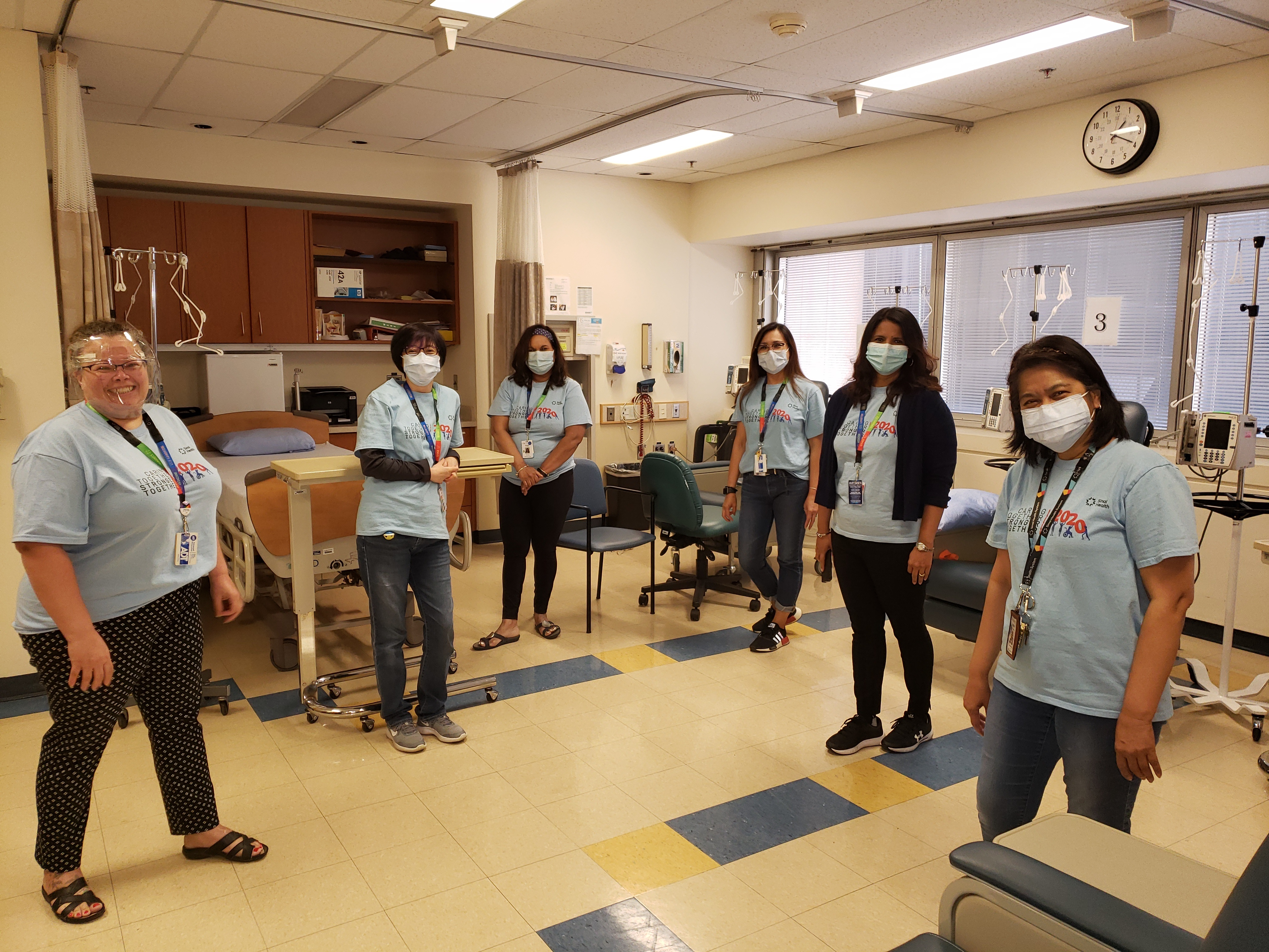 hospital employees wearing the same shirt and procedure masks standing in a hospital unit facing the camera.