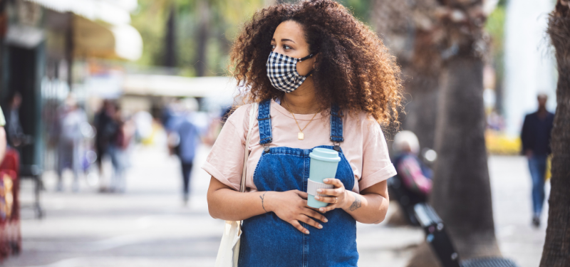 Woman is wearing a mask and holding coffee cap