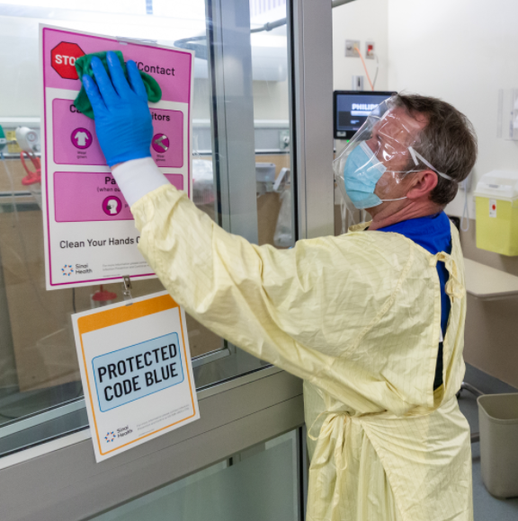 A clinical service assistant in full PPE washes the doors in Mount Sinai's Emergency Department