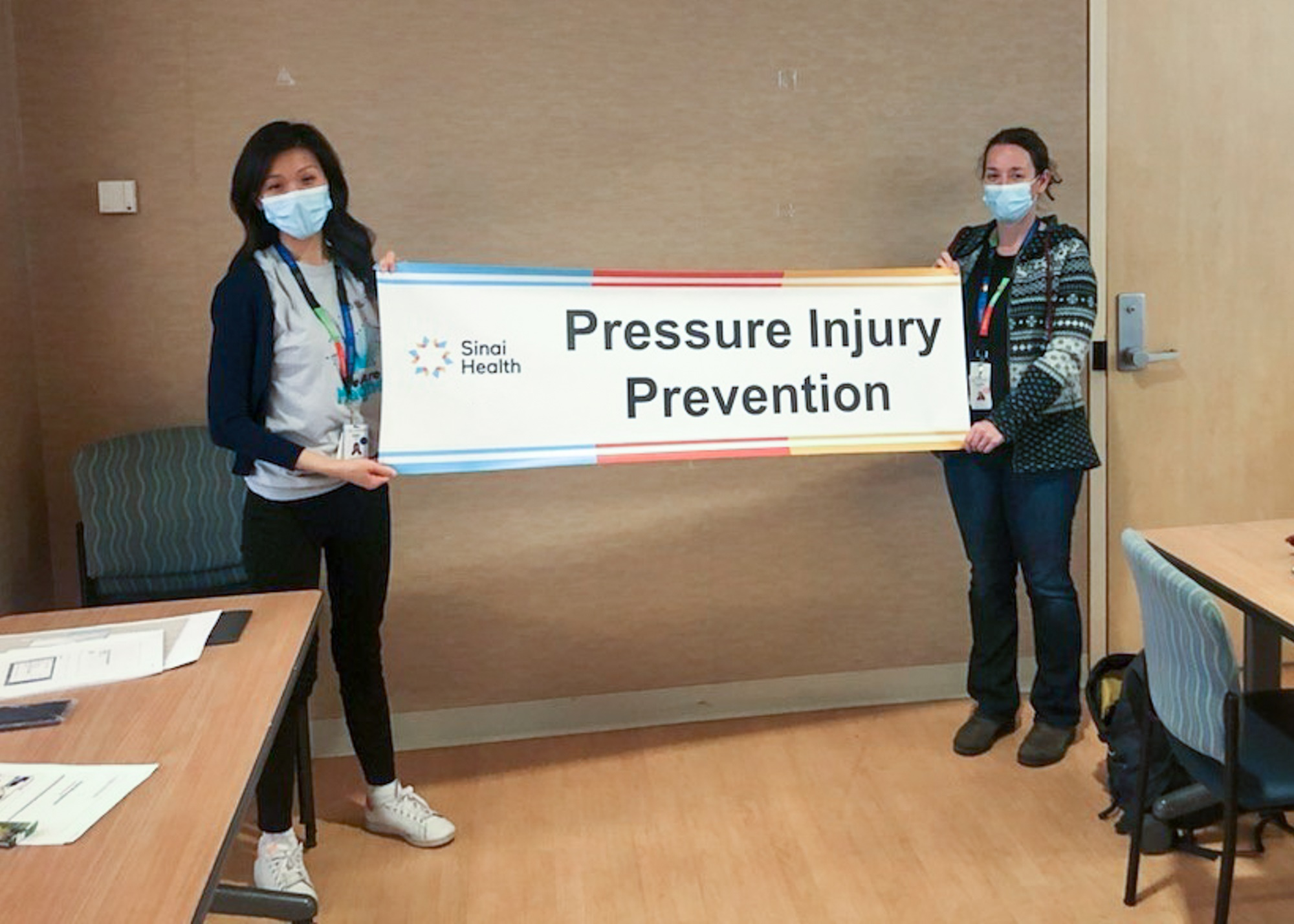 Two employees holding up a banner that says Sinai Health Pressure Injury Prevention