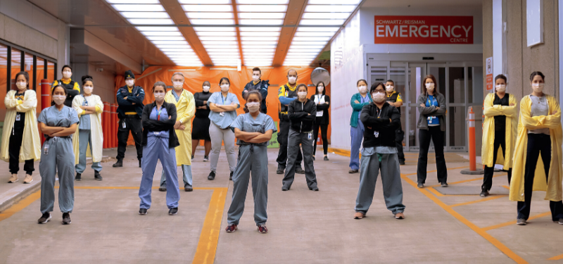 Health care workers all standing socially distantly with their arms crossed facing the camera