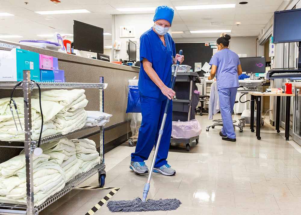 Clinical service assistant cleaning up the floor in the clinical care areas