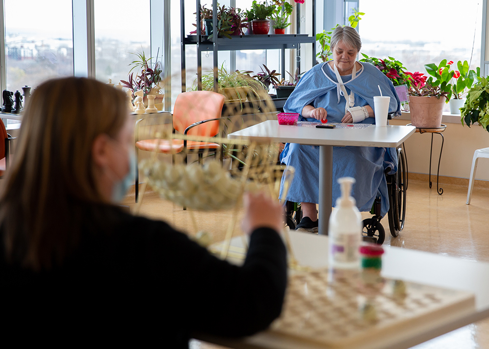 Patients doing activities such as painting and bingo in physically distanced environments
