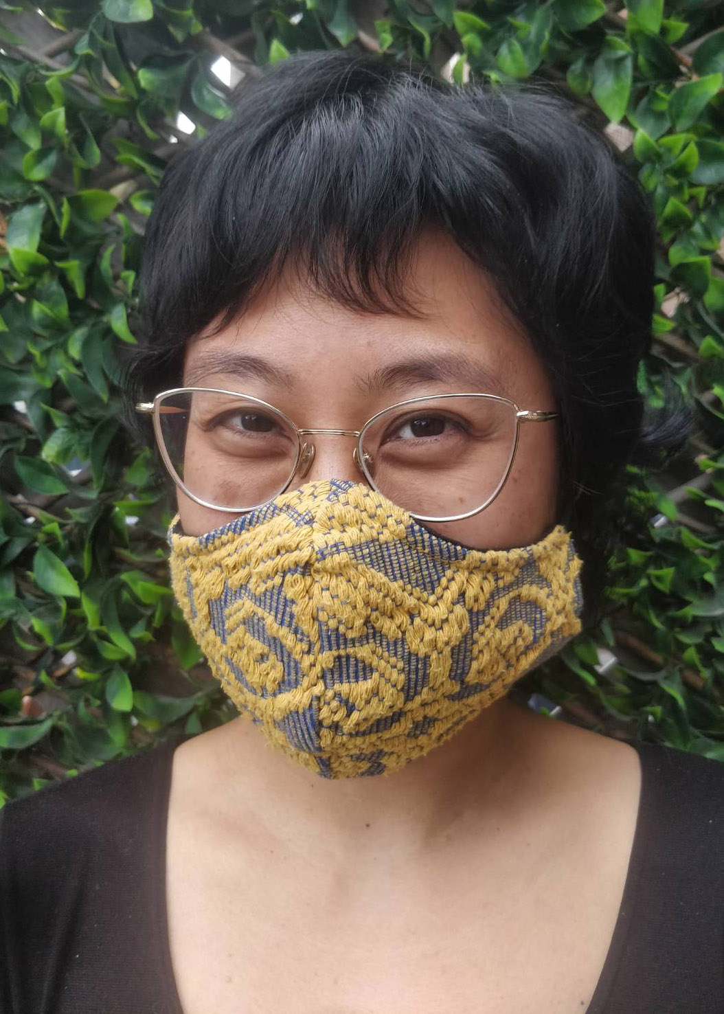 woman in her thirties smiles while wearing a decorative mask