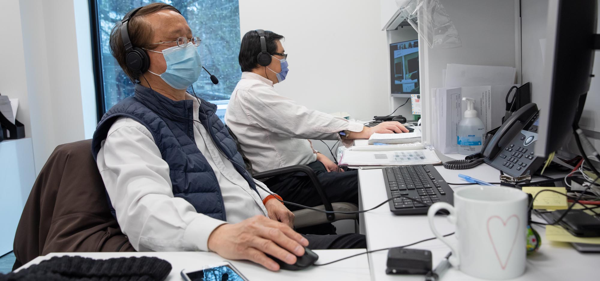 2 men in masks, looking at their computers